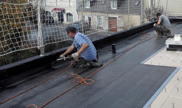 Deux employés de CLS Etanchéité effectuent des travaux d'étancheité sur un toit terrasse près de Tours (37)