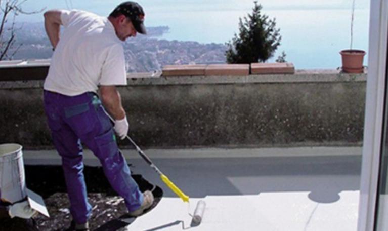 Une personne repeint une toiture terrasse