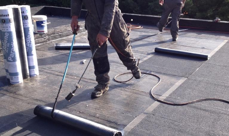 Deux personnes effectuent l'entretien de toiture terrasse